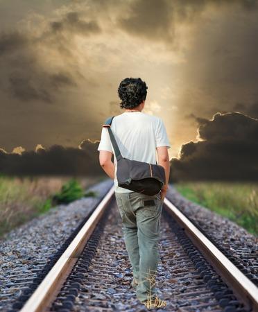 man walking on the railway tracks photo