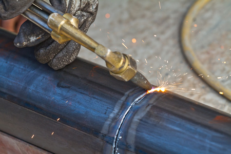 slag: worker using torch cutter to cut through metal Stock Photo