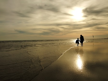 The silhouette of family watching the sunrise on the beach photo