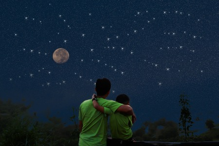 Father and son sit and watch the stars looking at the moon Stock Photo