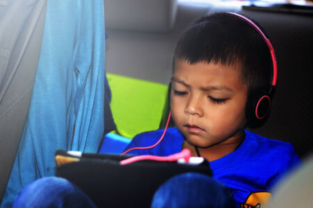 cute teen boy: Cute teen boy listening to music with headphones and tablet outside.