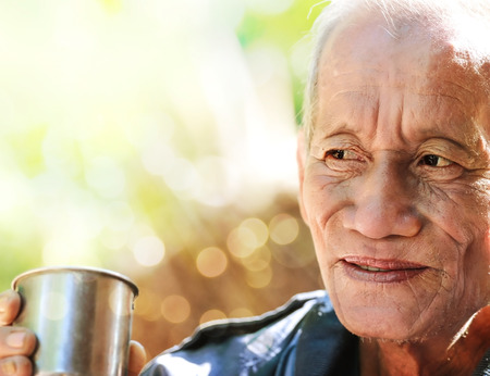 cheerful old man holding a cup of coffee photo