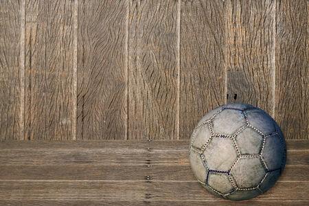 raged: Old used football or soccer ball on cracked asphalt