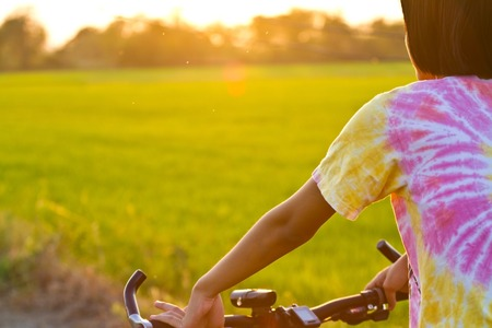 girl cycling in rice fields. photo