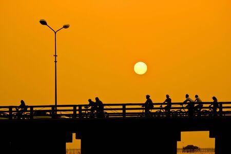boys and girls: Men riding bicycles on the bridge ,sunset Stock Photo