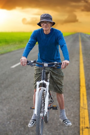 Active senior man riding a bicycle on countryside photo