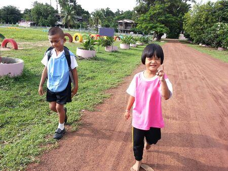 schoolkids: Schoolkids walking to school on country road under the sunlight