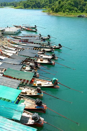 Long-tail boat parked in a row to stay Chiew Lan Dam. Surat Thani Province. photo