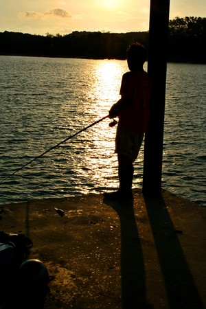 Een radeloos jonge man visserij op Rawai Beach, Phuket, Thailand