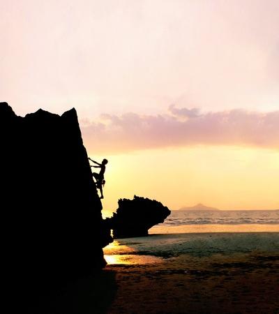 Silhouet van een man rotsklimmen bij zonsondergang.