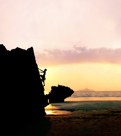 Silhouette of a man rock-climbing at sunset.