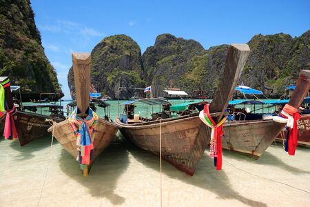 longtail: Long Tail Boat at Maya Bay, Krabi, Thailand  Crystal Clear Waters, Clear Skies and Perfect Scenery  A long tail boat sits in Maya Bay, Koh Phi Phi Ley, Thailand  The place where the movie the Beach was filmed