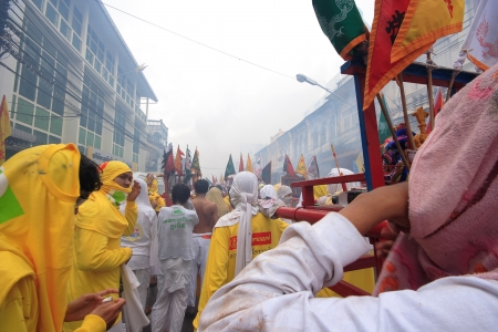 Devotees of a Taoist shrine carry a God idol on a palanquin while participating in a street procession of the Phuket Vegetarian Festival 2012  Photo taken on  October 18th, 2012