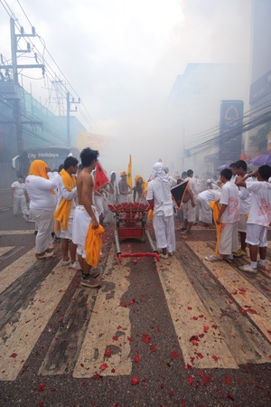 PHUKET - OCT 19: Devotees of a Chinese Taoist shrine carry a palanquin housing a Chinese God idol in a street procession to mark the Phuket Vegetarian Festival on Oct 19, 2012 in Phuket, Thailand.