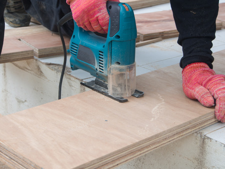 sawhorse: A carpenter is sawing along a straight pencil line.