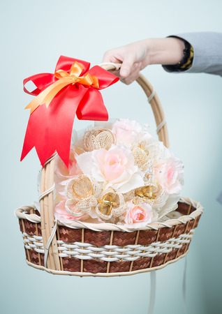 Woman hand holding a basket of flowers photo