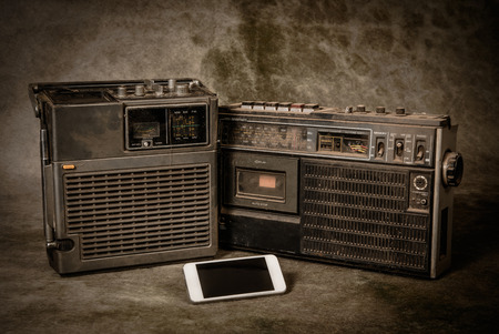 stereo cut: the still life retro ghetto blaster and new smartphone on grunge background