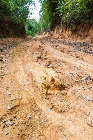 clay stone road in jungle: road landslide damage  Stock Photo
