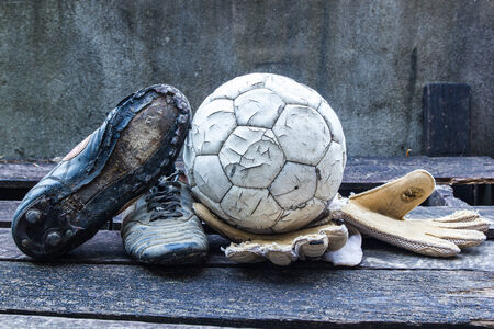 football cleats: Equipment used old football player On weathered wooden table  Stock Photo