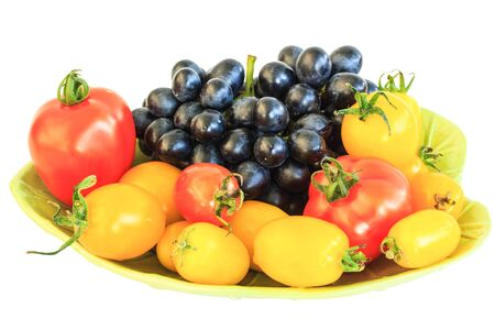 asterids: Tomatoes and grapes on a plate isolate on white background.