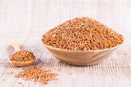 gi: Sangyod brown GI rice in a wooden bowl. Stock Photo