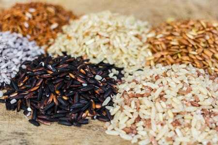 Various rice types each within an individual pile on rustic wood photo