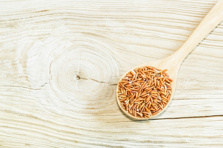 gi: Sangyod brown GI rice on wooden spoon on wooden  background. Product of Thailand, Asia. Stock Photo