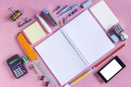 writing implements: High Angle View of Colorful School Supplies Organized by Type Around Note Book Open to Blank Page Arranged on pink fabric