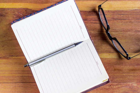 Open diary or office journal with a double page lined blank spread for your text with a ballpoint pen and glasses on a wooden desk, overhead view
