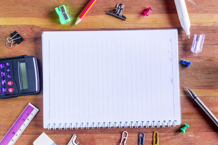 writing implements: Assorted Office Supplies on Wooden Table, Emphasizing White Blank Notepad at the Center with Copy Space for Texts.