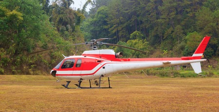 embark: Red helicopter at heliport in mountain