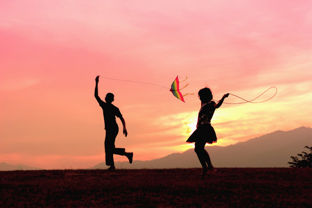 A brother getting a kite to fly and sister rope jumping during sunset.