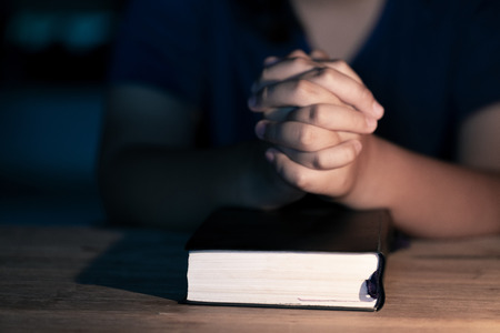Soft focus on a hand of woman while praying for christian religion with blurred of her body background , Casual woman praying with her hands together over a closed Bible