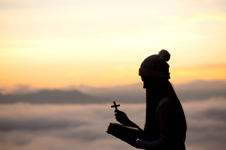 Silhouette off woman hands holding wooden cross on sunrise background, Crucifix, Symbol of Faith. Stock Photo