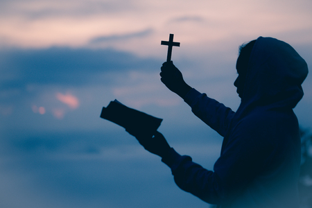 Silhouette of teen girl hands holding wooden cross and bible on sunrise background, Crucifix, Symbol of Faith.