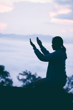 Silhouette of teen girl kneeling and praying over beautiful sunrise background. 免版税图像