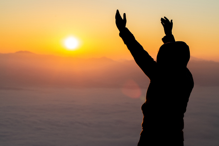 Girl silhouette raising hands in sunset light., Crucifix, Symbol of Faith.