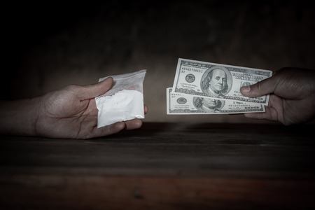 Hand of addict man with money buying dose of cocaine or heroine or another narcotic from drug dealer. Drug abuse and traffic concept. Foto de archivo