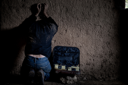 Drug dealer under arrest confined with handcuffs and hands at his back, standing next to a wall. Focus on the handcuffs chain