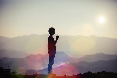 Glaube des christlichen Konzepts: Spirituelles Gebet überreicht Sonnenschein mit verschwommenem, wunderschönem Sonnenuntergangshintergrund