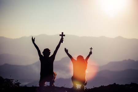 Father and little daughter silhouettes praying at sunset on the mountain Stock Photo