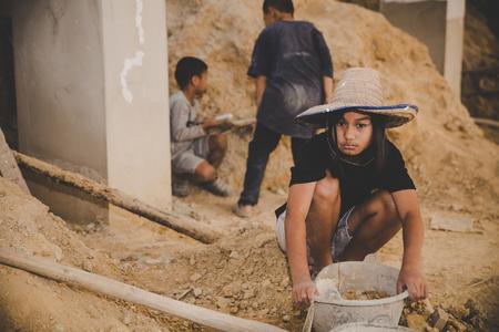 Los niños y niñas trabajan en la estructura de un edificio comercial, el concepto del Día Mundial contra el Trabajo Infantil. Foto de archivo