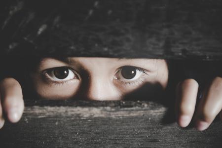 Niña aburrida, niño asustado está espiando a través de una valla de madera. Niña asustada. Emoción humana, expresión facial. Niño triste al aire libre. Foto de archivo