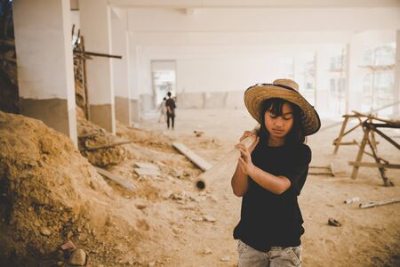 Little child labor working in commercial building structure, World Day Against Child Labour concept. Stock Photo