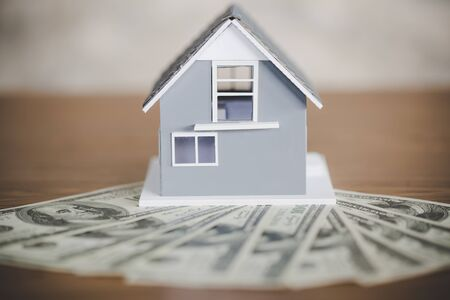 Classic house model on us dollar on wooden table