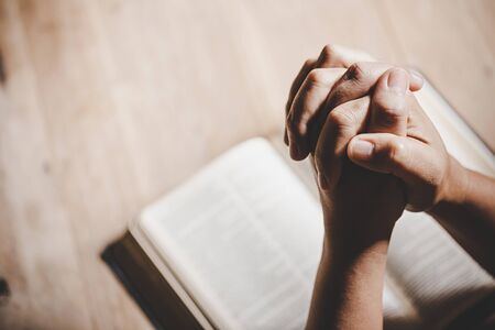 Spirituality and religion, Hands folded in prayer on a Holy Bible in church concept for faith. Stock Photo