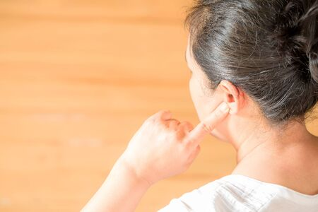 Female having ear pain touching his painful head on light brown background 스톡 콘텐츠