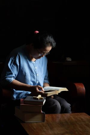 Christian women read the scriptures in the house with three books with a cross on the top, placed on the table. 写真素材