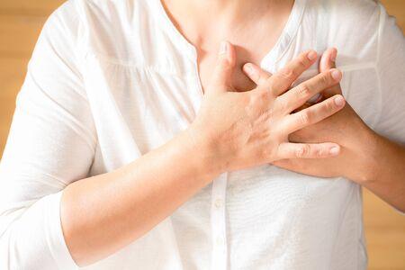 Kobieta ściska klatkę piersiową, ostry ból możliwy zawał serca