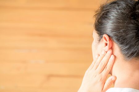 Female having ear pain touching his painful head on light brown background Banque d'images